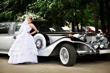 limousine: Luxury bride in a white wedding dress about big retro limousine