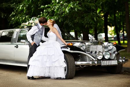 Happy groom and bride about retro limousine photo