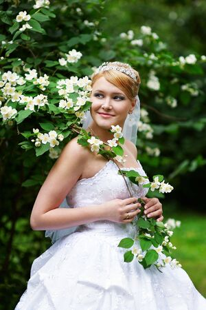 Happy bride in a wedding dress and a branch with white flowers Stock Photo