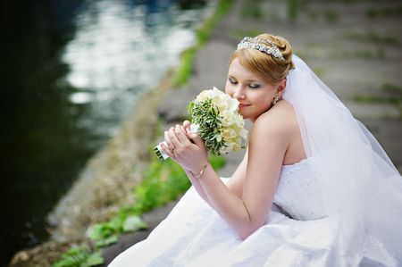 Happy bride in wedding dress near lake with bouquet of flowers