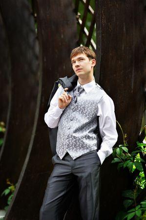 Young groom in park in wedding suit