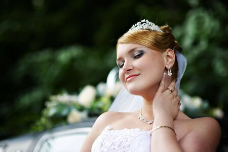 Luxurious bride with a haughty look in a white wedding dress photo