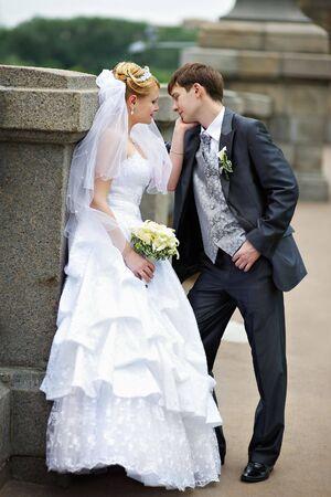 Happy bride and groom at a wedding walk on bridge photo