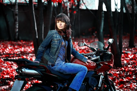 The mysterious girl on a red motorcycle among the fantastic red nature