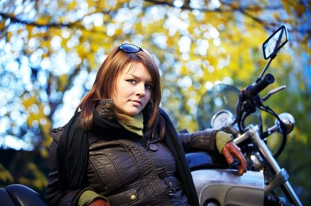 The girl the brunette about a motorcycle in autumn park photo