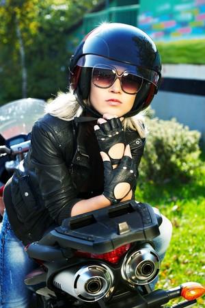 krachtige vrouw: De blonde in een helm op een moderne motor fiets  Stockfoto
