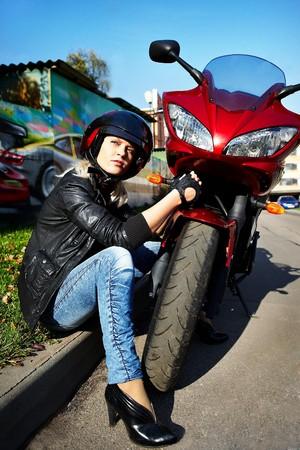 krachtige vrouw: De blonde in een helm over een rode motor fiets