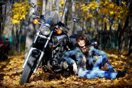 krachtige vrouw: Het meisje op de aarde over een motor fiets Stockfoto