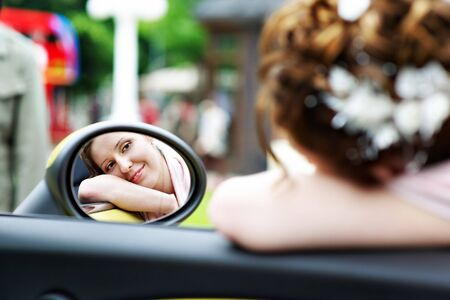 Happy bride looks in the mirror of the car at the wedding walk photo