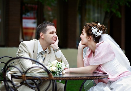 Happy bride and groom sit at a table in a cafe photo