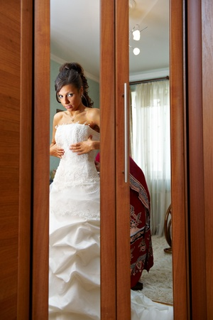 Charges the bride and dress up wedding gown in house of parents