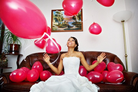 Happy bride is playing with red balls on sofa photo
