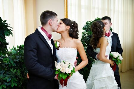 Romantic kiss bride and groom in wedding palace photo