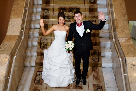 Fun bride and groom in stairs of wedding palace