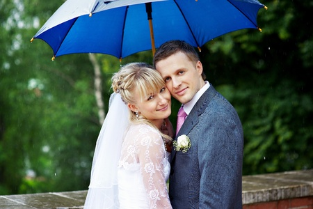 Happy bride and groom at a wedding under an umbrella in rainy weather