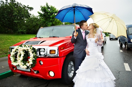 Happy bride and groom at a wedding a walk around the red limousine photo