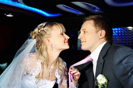 Happy bride and groom in a wedding limousine