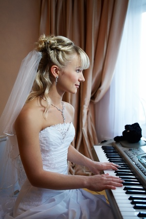 Beautiful Bride plays on an electronic piano Stock Photo - 10552901