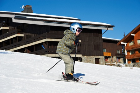 positiv: Small child skiing on snow slope in resort