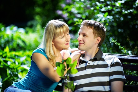 Boy and girl on a romantic date on a park bench photo