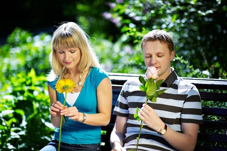 Boy and girl with flowers on a romantic date on a park bench photo