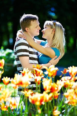 Lover man and girl among red yellow flowers in spring park Stock Photo - 10697883