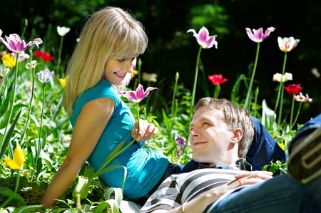 Happy woman and man among flowers in spring park Stock Photo