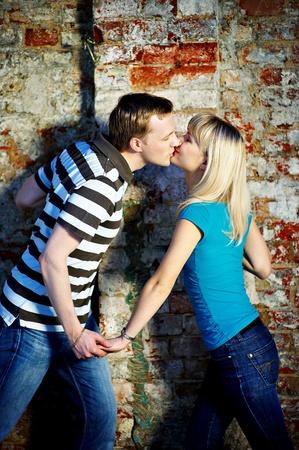 bondad: Rom�ntico beso cerca de la pared de ladrillo antiguo Foto de archivo