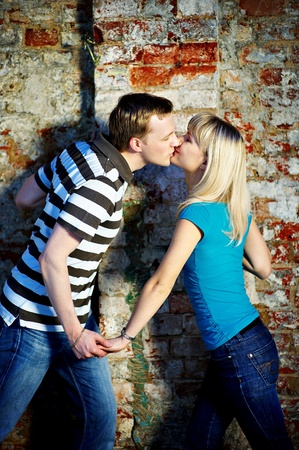 a young old couple: Romantic kiss near old brick wall