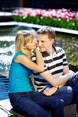 Happy couple near pool in park photo