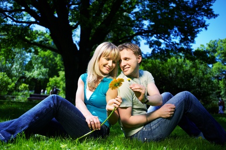 Happy man and woman with flowers in park photo
