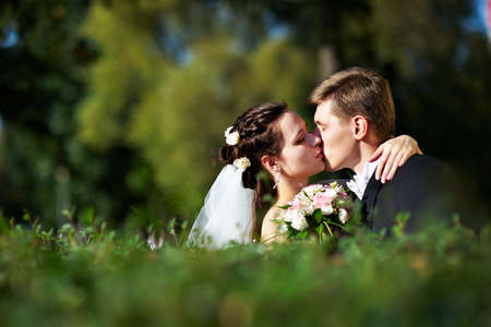 Romantic kiss the bride and groom at the wedding walk photo