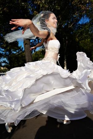 Счастливая свадьба невеста танцует в парке летом Фото со стока