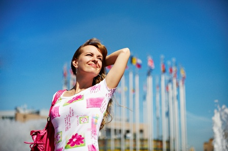 Young cheerful woman on square of Moscow city on background of sky Stock Photo - 10811436