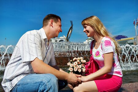 Romantic dating young guy and girl in city square in Moscow