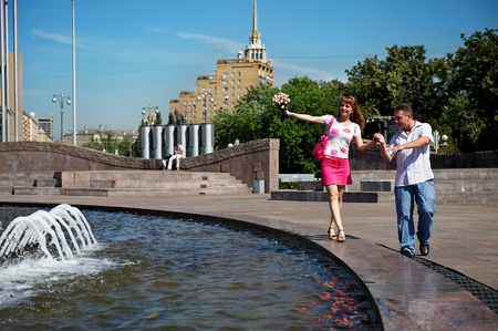 Dating young men and women lovers in city park Stock Photo