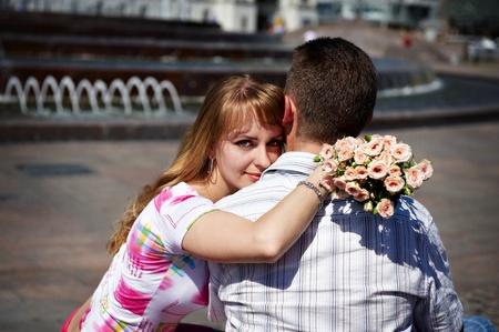 Романтические объятия парень и девушка по отрасли в городском парке