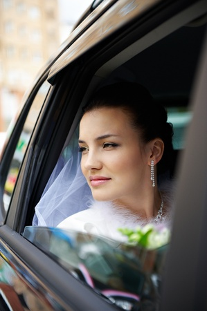Happy bride in window a wedding limo photo