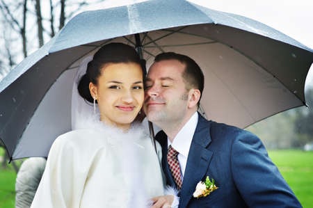 Happy bride and groom at wedding walk with umbrella in the rain photo
