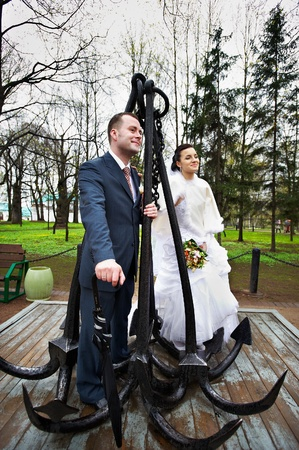 Happy bride and groom in a park near the monument with anchors photo