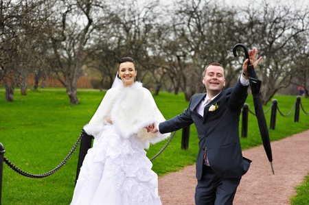 Funny couples in wedding walk in park photo