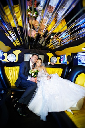 The bride and groom in a wedding limousine with yellow and black colors photo
