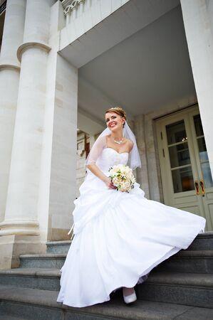 Happy bride with wedding bouquet on wedding walk photo
