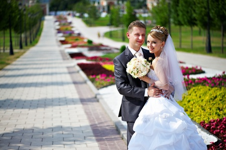 Happy bride and groom at a wedding a walk in the park surrounded by flowers