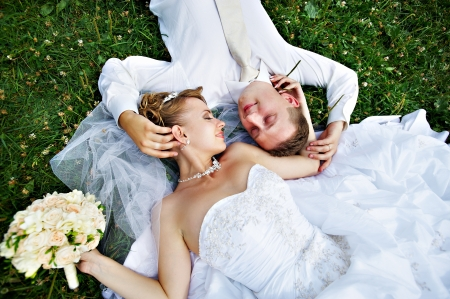 Happy bride and groom on grass in park photo
