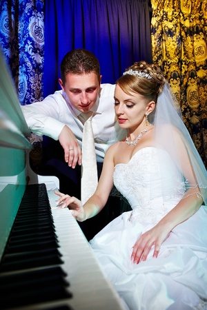Bride and groom at piano in banquet photo