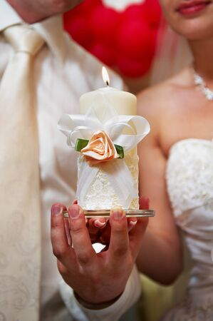 Candle in the hands of the newlyweds symbolizes hearth and well-being of the family. Stock Photo - 11312368