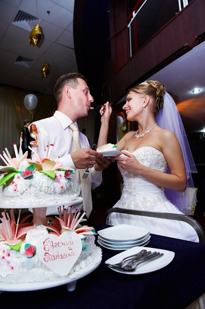 Happy bride feeding her fiance wedding cake