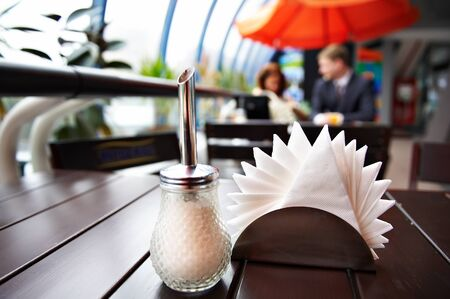Sugar bowl and napkins in cafes and in the background a man and a woman at a table for lunch  photo