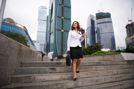 descends: Young business woman descends the stairs to the street  Stock Photo